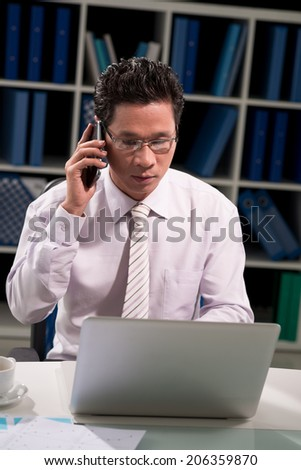 Businessman talking on the phone while working on the laptop - stock photo