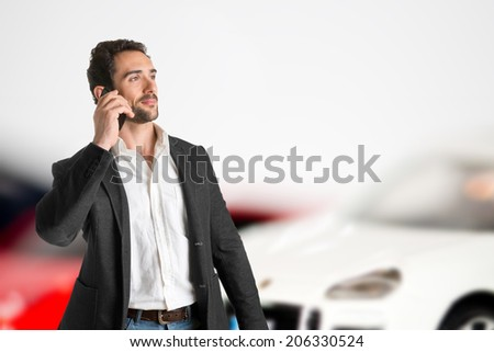 Businessman talking on the phone with cars behind him - stock photo