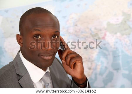 Businessman talking on the phone with worldmap in background - stock photo