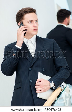 Businessman talking on the phone. Young businessman standing on the steps and keeps the tablet while his colleagues talking to each other - stock photo