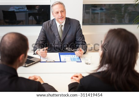 Businessman talking to a couple in his office - stock photo