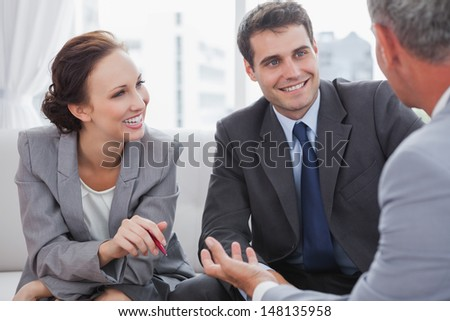 Businessman talking to his partners in cosy meeting room - stock photo