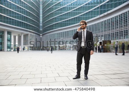 businessman talking to mobile outside office building