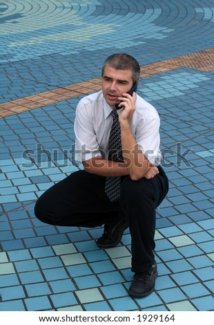 Businessman talking to the phone in paved square.