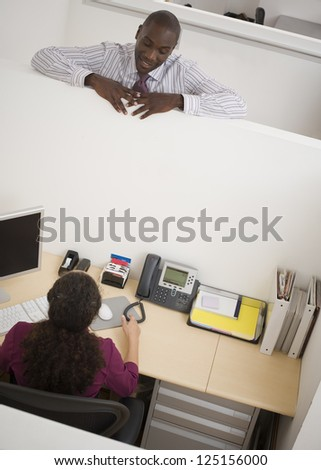 Businessman talking to woman in a cubicle - stock photo
