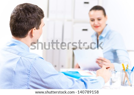 Businessman talking with a colleague in the office, discussing reports