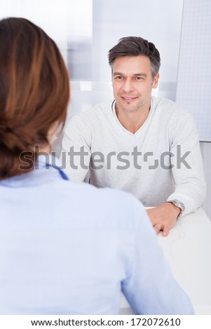 Businessman Talking With Female Colleague In Office - stock photo