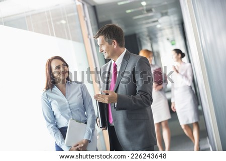 Businessman talking with female colleague while walking in office corridor - stock photo