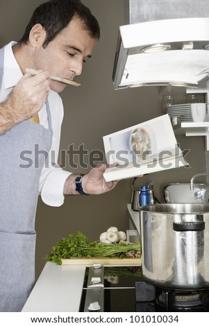 Businessman tasting his food while using a recipe book to cook at home. - stock photo