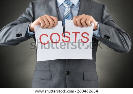 Businessman Tearing The Word Costs On Paper Over Gray Background - stock photo