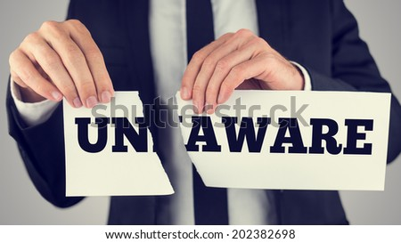 Businessman tearing up a sign saying - Unaware - conceptual of successfully overcoming ignorance, toned retro or instagram effect. - stock photo