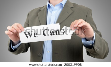 Businessman tearing up a sign saying - We Can - stock photo