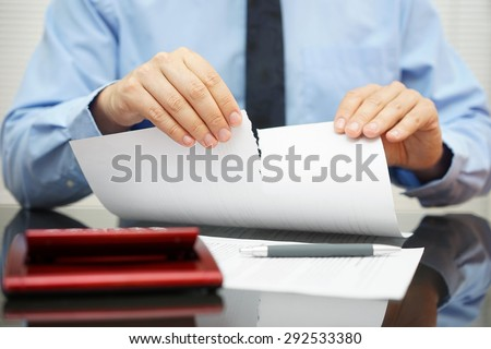 businessman tears document in office - stock photo