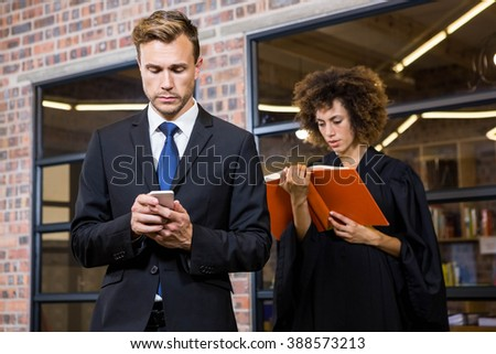 Businessman text messaging on smartphone and lawyer reading law book