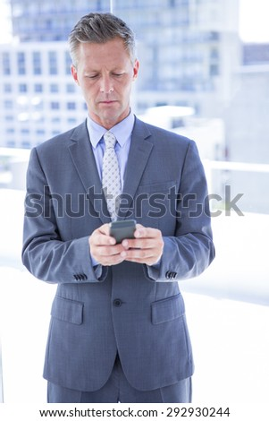 Businessman texting with his smartphone in the office - stock photo