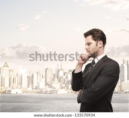 businessman thinking and city on background - stock photo