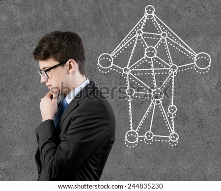 businessman thinking and drawing arrows on wall - stock photo