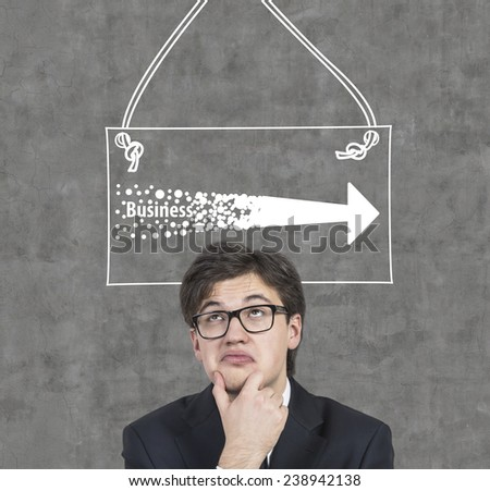 businessman thinking and drawing two arrows on wall - stock photo