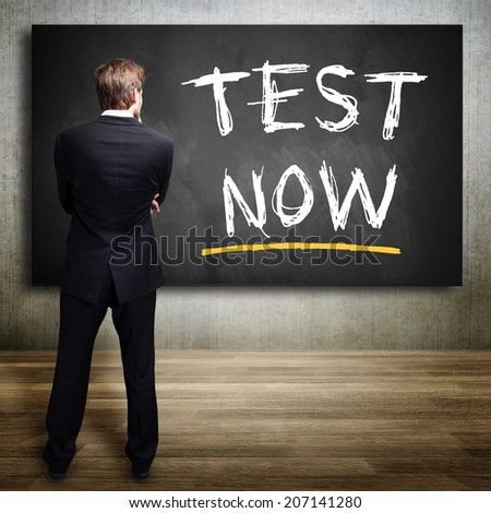 """businessman thinking and looking at a """"Test Now"""" sign - stock photo"""