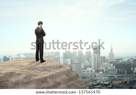 businessman thinking and looking at city in distance