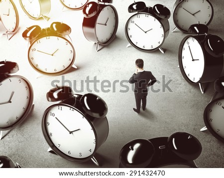 businessman thinking and many big clock  on floor