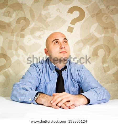 Businessman thinking and questioning, looking at question marks around his head.