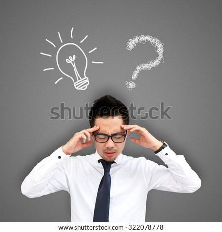 Businessman thinking between light bulb and question mark - stock photo