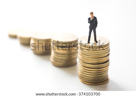Businessman thinking in front of coins stacks. Investment concept.