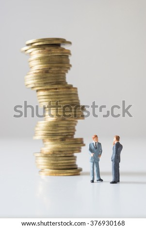 Businessman thinking in front of coins stacks. Investment concept. - stock photo