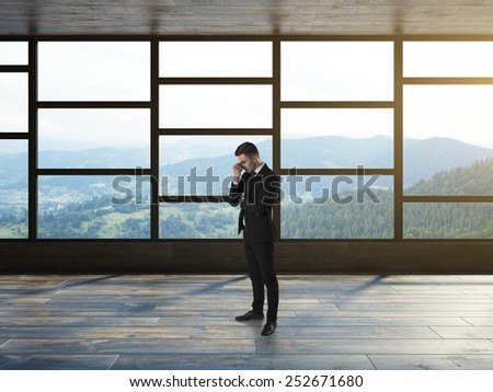 Businessman thinking in modern empty interior - stock photo