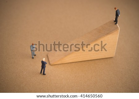 Businessman thinking or making decision in front of slope ladder wood block  - stock photo