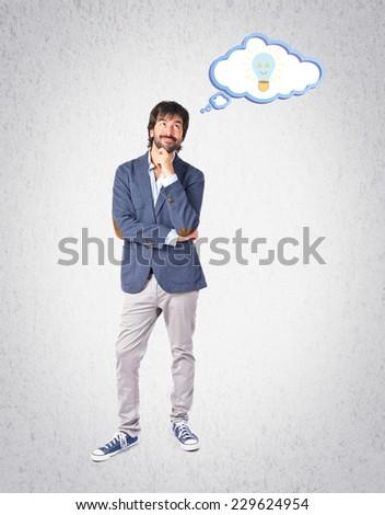 Businessman thinking over grey background - stock photo