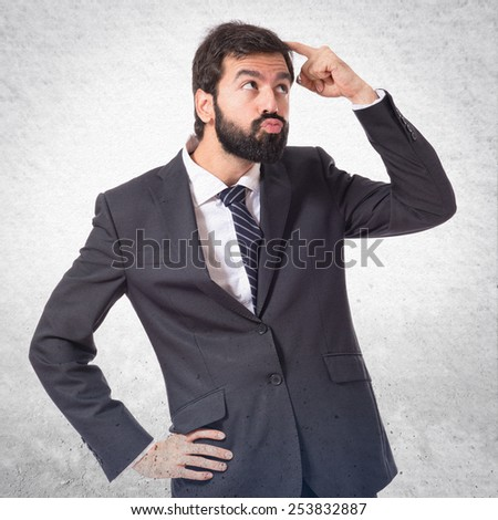 Businessman thinking over textured background
