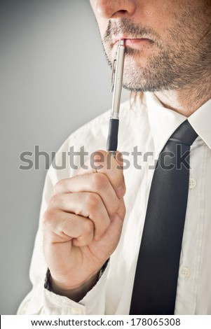 Businessman thinking with pencil in his mouth. Portrait of thoughtful business person.