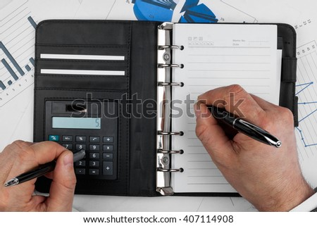 Businessman thinks on the calculator and  writes, as background - stock photo