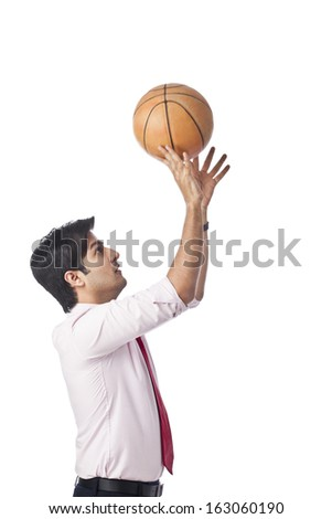 Businessman throwing a basketball - stock photo