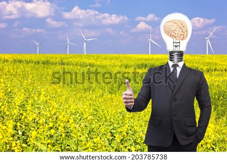 businessman thumb up and head brain inside a light bulb idea concept for success business creativity wind turbines in a flower field eco power concept  - stock photo