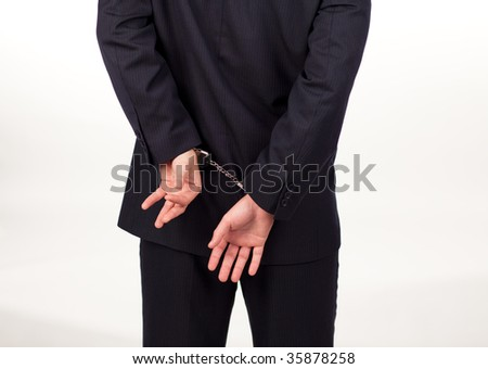 Businessman tied up in hand cuffs