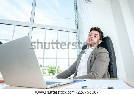Businessman tired of working at a laptop. Young successful businessman looks and works in the laptop while sitting at a desk and a laptop in the office