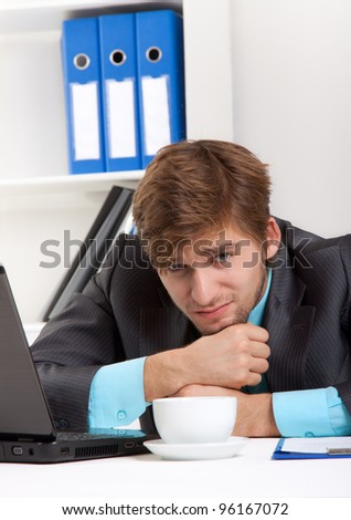 businessman tired stressed, depressed sitting at desk in office, handsome young business man working problem crisis, overworked, wear elegant suit - stock photo