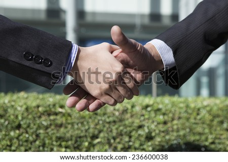Businessman to shake hands outdoors - stock photo