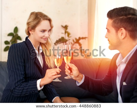 Businessman toast with businesswoman in office in sunset