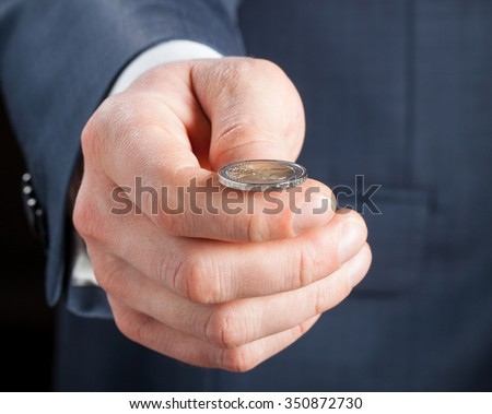 Businessman tossing a coin - stock photo