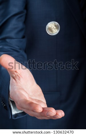 Businessman tossing a coin - closeup shot - stock photo