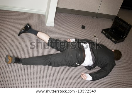 businessman totally collapsed on floor with briefcase open - stock photo