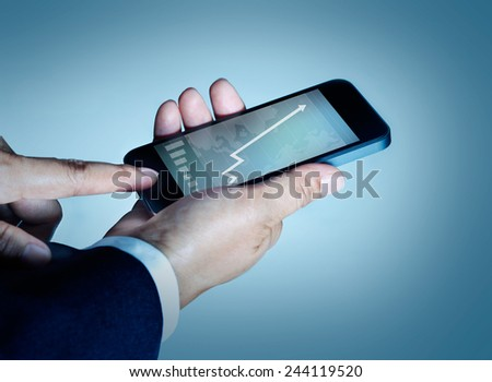 businessman touch mobile phone graph and statistics rising on screen  - stock photo