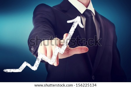 Businessman Touching a Arrow Indicating Growth on navy blue background - stock photo
