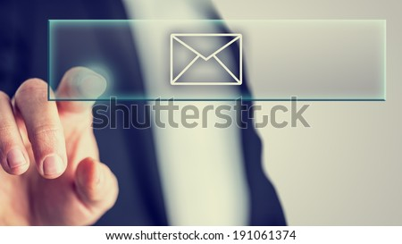 Businessman touching a mail icon in a navigation bar on a virtual interface to access online communication, retro vintage toned image. - stock photo