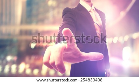 Businessman touching a touch screen on blurred city background