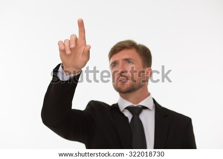 Businessman touching a virtual cyberspace screen isolated on white. Serious man in black suit trying to make all calculation. - stock photo